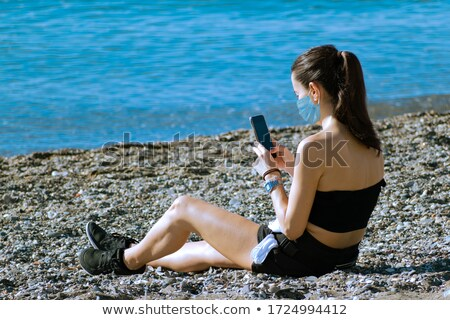 Vacationing Woman Wearing Face Mask on Sandy Beach. Stock photo © feverpitch