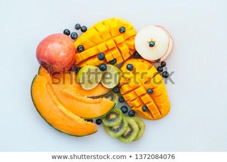 Assortment of juicy tropial fruit on white background. Slices on melon, orange mango, kiwi, lime, bl Stock photo © vkstudio