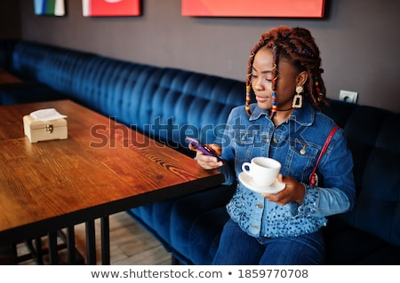Young girl with dreadlocks posing indoors. Stock photo © deandrobot