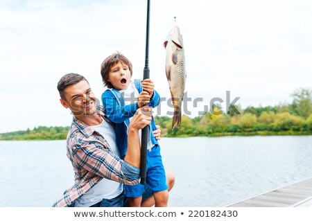 Family outdoor recreational activities, parents looking at son with flying kite, recreation time Stock photo © robuart