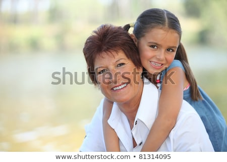 Young girl riding piggy-back on her grandmother's back Stock photo © photography33