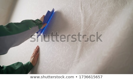 Woman smoothing wallpaper Stock photo © photography33