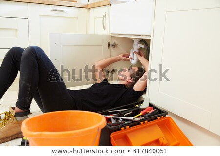 Female plumber fitting a kitchen sink Stock photo © photography33