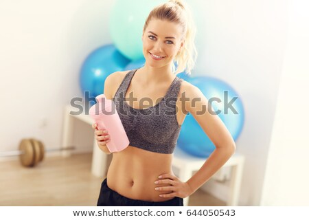 smiling woman holding shaker with water stock photo © deandrobot