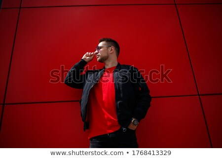 Young sports man standing near grey wall outdoors Stock photo © deandrobot