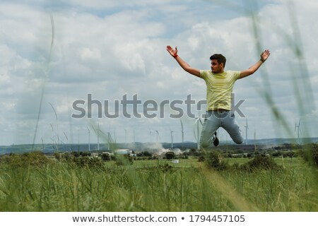 Man jumping in Front of Wind Turbines Stock photo © IS2
