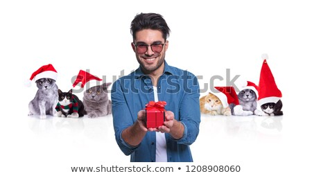 smiling casual man offers christmas present with santa cats behi stock photo © feedough