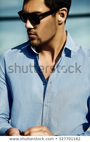 portrait of confident handsome businessman in sunglasses on black background with hands in pockets stock photo © traimak