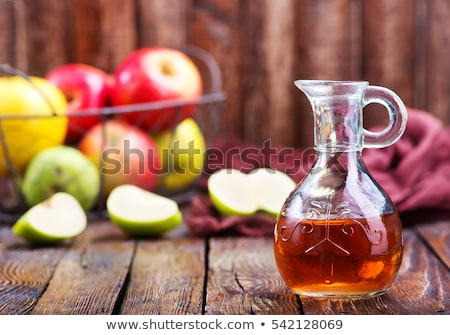 Bottle and glass of homemade organic apple cider with fresh apples in box on wooden background Stock photo © DenisMArt