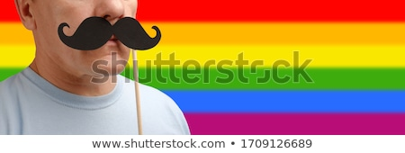 close up of couple with gay pride rainbow ribbons stock photo © dolgachov