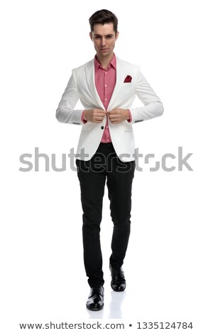 serious young elegant man closing his coat and walking  Stock photo © feedough