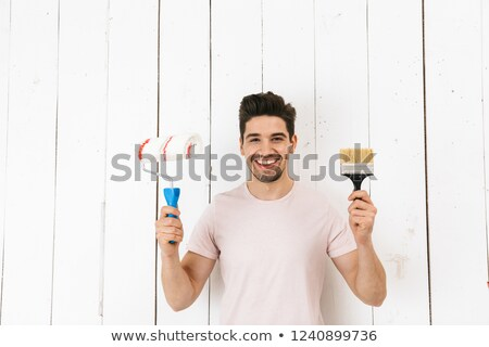 Stockfoto: Image Of Joyful Man 20s Painting White Wall And Making Renovatio
