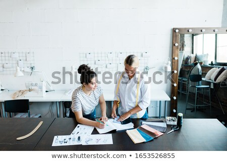 Two young fashion designers choosing textile for new seasonal collection Stock photo © pressmaster