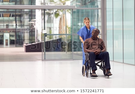 Front view of senior woman pushing senior man in a wheelchair on sunny day at park Stock photo © wavebreak_media