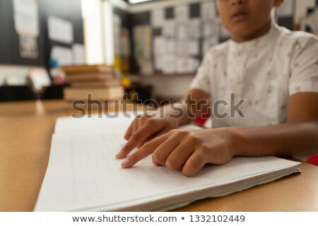 Mid section of blind focused mixed-race schoolboy reading a braille book in classroom at elementary  Stock photo © wavebreak_media