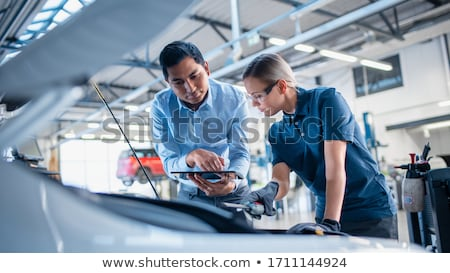 mechanic man with lamp repairing car at workshop Stock photo © dolgachov
