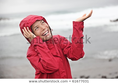 Girl enjoying the rain and having fun outside on the beach  a gray rainy Stock photo © Lopolo
