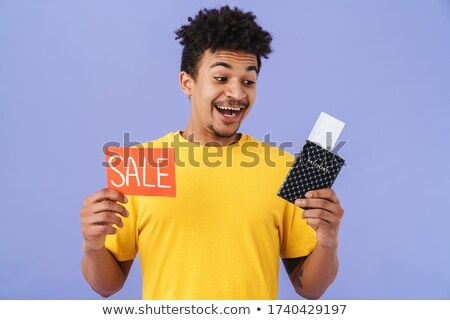 Photo of african american man holding sale card and passport Stock photo © deandrobot