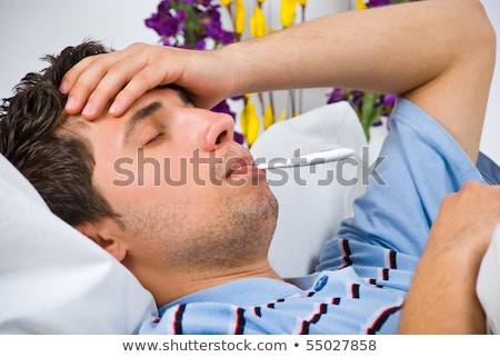 close up of young man lying down in bed taking temperature and h stock photo © dacasdo