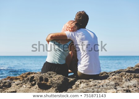 Young couple talking to a rock by the sea stock photo © Kotenko