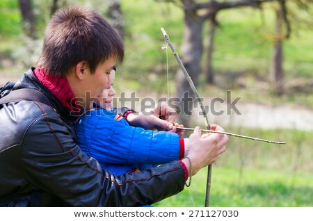 A father teaching his son how to shoot bow. Stock photo © photography33
