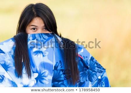 Playful young girl peeking over her umbrella Stock photo © smithore
