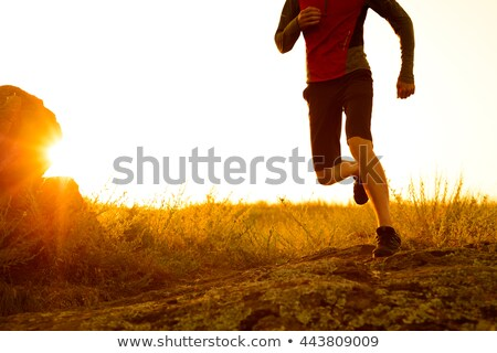 Stock photo: Silhouette of Man Running on the Rocky Trail at Sunset. Legs Close Up. Extreme Sports.