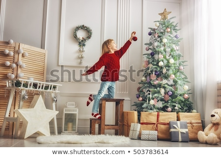 beautiful girl decorating christmas tree Stock photo © PetrMalyshev