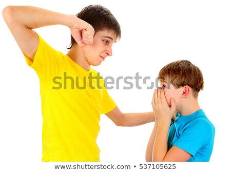 Angry young man standing and threatening with fist Stock photo © deandrobot
