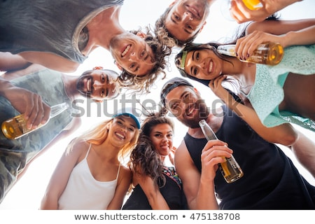 Low angle view of happy guys  standing together in a circle agai Stock photo © meinzahn