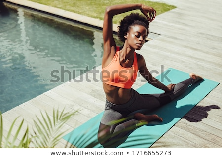 Woman practicing yoga on at poolside Stock photo © wavebreak_media