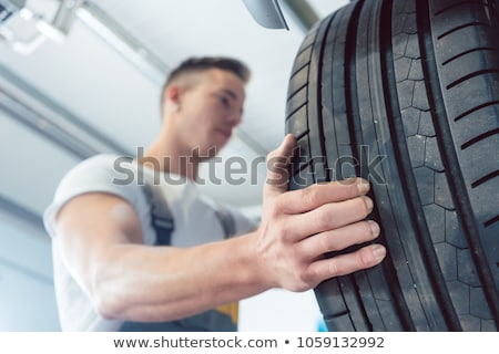 Low-angle view of the hand of a skilled auto mechanic holding a tire Stock photo © Kzenon