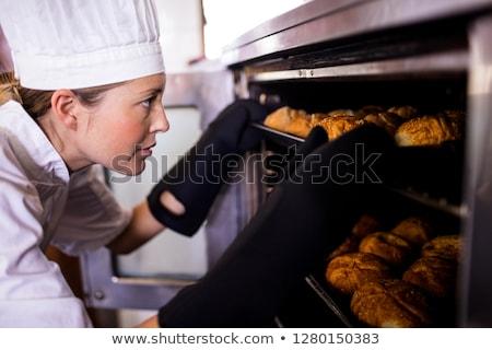Female chefs putting baking tray of kaiser rolls in oven at kitchen Stock photo © wavebreak_media