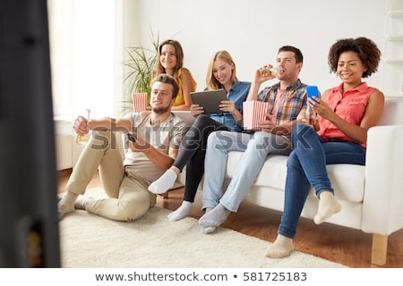 friends with smartphone watching tv at home stock photo © dolgachov