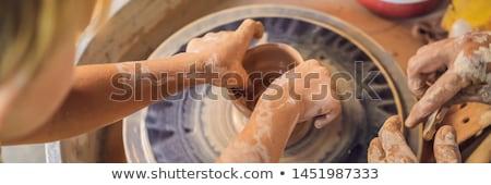 Father and son doing ceramic pot in pottery workshop Stock photo © galitskaya