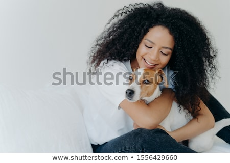 Happy African American woman expresses love to dog, embraces pet, dressed in casual wear, sit on com Stock photo © vkstudio