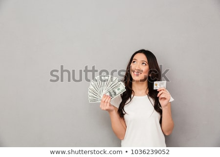 Image of young asian woman holding money banknotes and credit ca Stock photo © deandrobot