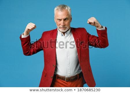 Mature Man Working Out Biceps On Grey Background Stock photo © Jasminko