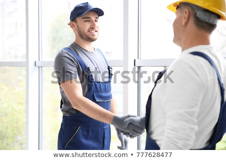A construction worker and his trainee shaking hands. Stock photo © photography33