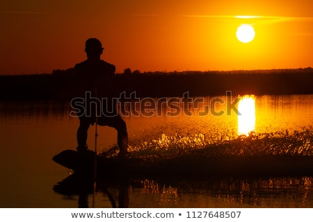 Silhouette Wakeboarder in action on sunset Stock photo © smuki