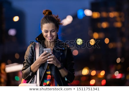 attractive young woman standing outdoors at night stock photo © deandrobot