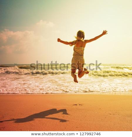 Lányok ugrik homok tengerpart nyár kék ég Stock fotó © IS2