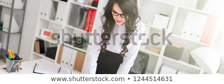 A beautiful young girl stands bent over an office desk, holds a pen in her hand and looks at the dia Stock photo © Traimak