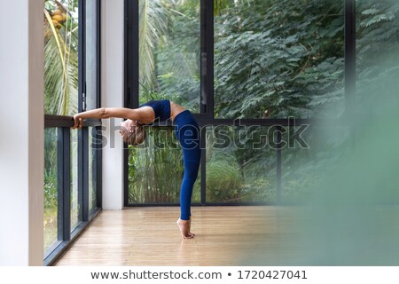 Back view of young sports woman warming up near window Stock photo © deandrobot