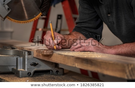 carpenter with ruler measuring plank at workshop Stock photo © dolgachov
