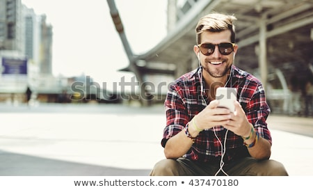 man with earphones and smartphone on city street Stock photo © dolgachov