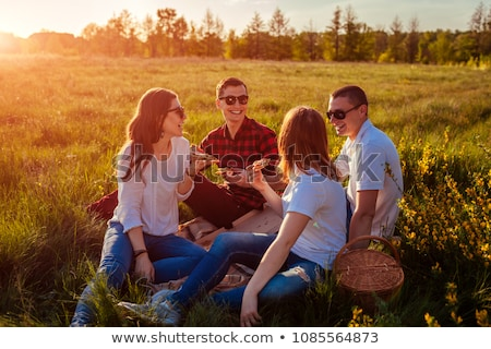 happy friends eating pizza at picnic in summer stock photo © dolgachov