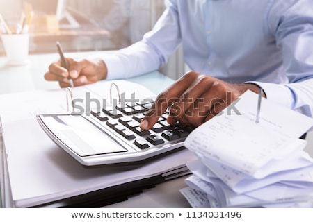 businessman calculating invoice using calculator stock photo © andreypopov