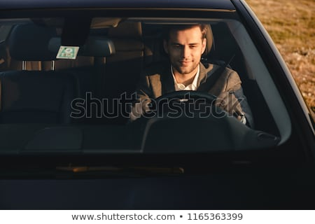 Front view of smiling bussinesman in suit driving his car Stock photo © deandrobot