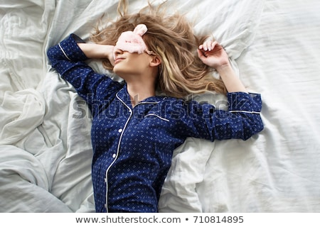 Young attractive woman, cheerful blonde in bed at home, starting a new day with a charge and cheerfu stock photo © ElenaBatkova